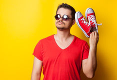 Guy with sunglasses and red gumshoes. Young guy in t-shirt with sunglasses and red gumshoes on yellow background Stock Image