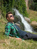 Guy in sunglasses relaxing in nature near the waterfall Royalty Free Stock Photos