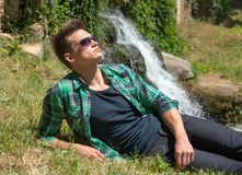 Guy in sunglasses relaxing in nature near the waterfall Stock Photography