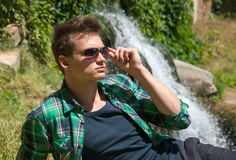 Guy in sunglasses resting in nature near the waterfall Royalty Free Stock Photography
