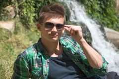 Guy in sunglasses resting in nature near the waterfall Stock Photos