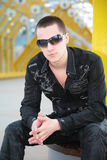 Guy in sunglasses sits on footbridge Stock Photos