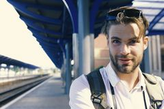 Guy with sunglasses waits for train, defocused. Missed train and travelling concept. Young man standing on platform. At train station, close up. Tourist with stock image