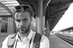 Guy with sunglasses waits for train, defocused. Missed train and travelling concept. Tourist with serious face and. Guy with sunglasses waits for train royalty free stock photos
