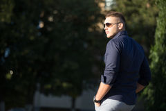 Guy in sunglasses walking in park Stock Images
