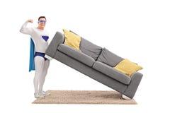 Guy in superhero costume lifting a sofa  Royalty Free Stock Photos