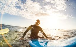 Guy surfer relaxing on surfboard at sunset in Tenerife. With unrecognizable people at surf boards on background - Sport travel concept Royalty Free Stock Images