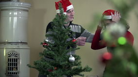 Guy surprises girl with Santa hat while decorating Christmas tree. Young romantic couple decorating Christmas tree by a fireplace with red and silver ornaments stock video footage