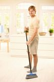 Guy sweeping the floor. Smiling guy sweeping the floor in living room, looking at camera, standing Royalty Free Stock Image