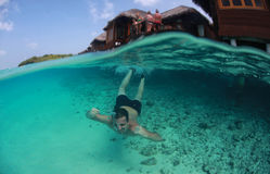 Guy swimming in the oceans sea, Maldives Royalty Free Stock Images