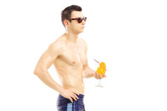 Guy in swimming shorts holding a cocktail Stock Image