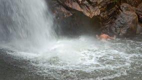 Guy Swims bajo flujo de la cascada en piscina del río por las rocas almacen de video