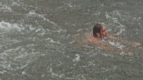 Guy Swims bajo flujo de la cascada en piscina del río por las rocas almacen de metraje de vídeo