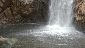 Guy Swims até a cachoeira alta espumosa espirra entre rochas video estoque