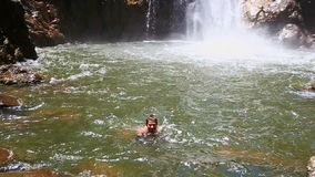 Guy swims near waterfall foamy base in pond among rocks. Caucasian guy swims near high waterfall foamy base in transparent pond among forestry green rocks stock video footage