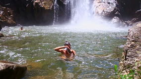 Guy swims near waterfall foamy base in pond among rocks. Caucasian guy swims near high waterfall foamy base in transparent pond among forestry green rocks stock video