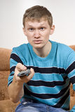 The guy switches the tv dissatisfied. The guy switches the tv angry, sitting on the couch Stock Photos