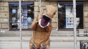 Guy in t rex costume prankster walking at city street crosswalk. With lots of parked cars. Sunny day. Slow motion stock video footage