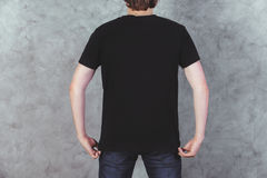 Guy in t-shirt back. Back view of young guy in casual black t-shirt and jeans on concrete wall background. Mock up Royalty Free Stock Images