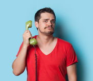 Guy in t-shirt with green retro dial phone Royalty Free Stock Photo
