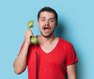 Guy in t-shirt with green retro dial phone Stock Image
