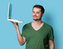 Guy in t-shirt with laptop computer Royalty Free Stock Image