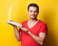 Guy in t-shirt with laptop computer Stock Photo