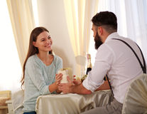 Guy at table, handing happy girl gift Royalty Free Stock Photo