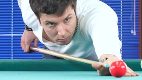 Guy takes aim, to make an impact on a billiard stock video footage