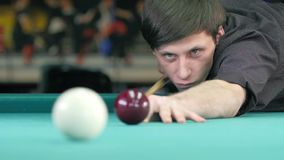 Guy takes aim, to make an impact on a billiard stock footage
