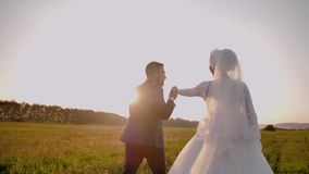 A guy takes his girlfriend`s hand at a stunningly beautiful meadow at sunset. Very nice plan stock video