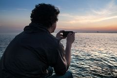 Guy takes on the phone a beautiful view sunset in the Bosphorus Strait. Istanbul royalty free stock images
