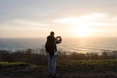 The guy takes a picture of the sunrise on the phone. Young slender guy taking pictures of the sunrise over the sea on the phone Royalty Free Stock Photos