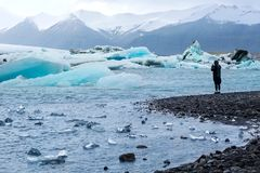 Guy takes pictures of the iceberg and the whole glacier in Iceland royalty free stock photography