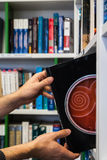Guy taking orange black book from the bookshelf in the library w Royalty Free Stock Photos