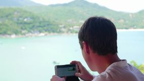 Guy is taking pictures on a smartphone panoramic view of the sea and mountains from a different viewpoint. Panoramic stock footage