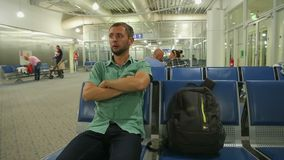 Guy taking seat at airport or railway station waiting room, transport service