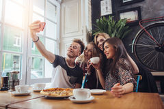 A guy taking a self-portrait with his female groupmates using his smartphone while hanging out in a coffee shop.  Royalty Free Stock Image
