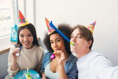 Guy is taking a selfie with his two friends. They are celebrating afro american girls birthday. People wears birthday. Hats. Also girls have whisltes stock photo