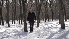 Guy is taking a walk. Serious guy is taking a walk in the park stock footage