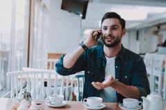 Guy Talk Smartphone Homem que senta-se no restaurante fotos de stock