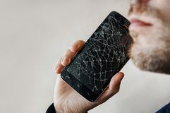 The guy is talking on the phone with a broken screen. Black smartphone with cracked glass in a man's hand. copy space. copyspace royalty free stock photos