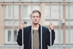 Guy with tattoos smokes cigarettes on the street, walks in the city on the street among high-rise buildings. Stands behind an iron grate from the front view Royalty Free Stock Photography