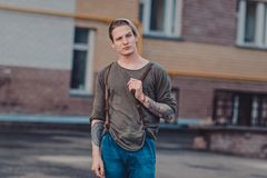Guy with tattoos smokes cigarettes on the street, walks in the city on the street among high-rise buildings. Vintage portrait of handsome serious thoughtful Stock Photography