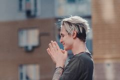Guy with tattoos smokes cigarettes on the street, walks in the city on the street among high-rise buildings. Vintage portrait of handsome serious thoughtful Royalty Free Stock Photos
