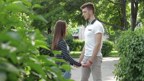 Guy teaches girl whirl in the Park. At beautiful summer day stock footage