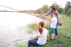 Guy is teaching his son how to catch fish right. Boy is holding long fish-rod. Guy is guide him. Young woman is sitting. Guy is teaching his son how to catch royalty free stock photography