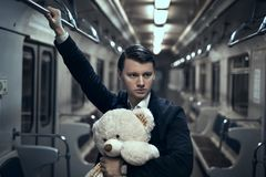 Guy with a teddy bear in the subway. In an empty car he is lonely, it makes him sad Royalty Free Stock Photo