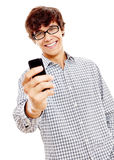 Guy texting on cell phone. Young hispanic man wearing wearing blue checkered shirt and black glasses reading something funny from his mobile phone and smiling Royalty Free Stock Images