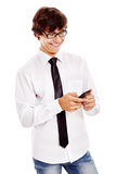 Guy texting on cell phone. Young hispanic man wearing white shirt, blue jeans, black tie and glasses reading something funny from his mobile phone and laughing Royalty Free Stock Image